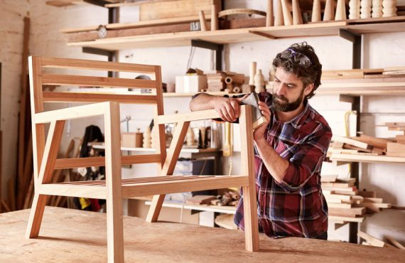 54601249 - serious furniture designer carefully sanding a chair frame that he is busy manufacturing in his woodwork studio, with shelves of wooden items behind him